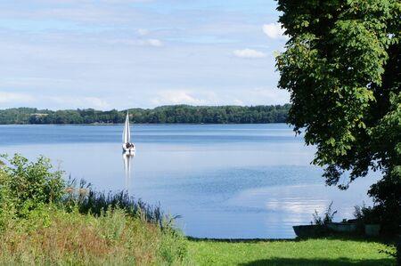 The sail boat on the lake Drawsko is a biggest freshwater lake in Czaplinek, Poland Stock Photo - 21948534