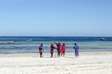 Zanzibar Nungwi Beach, Tanzania, Africa 11 December 2013   Group of male Masai on a beautiful Zanzibar beach in traditional clothes  Amaizing colors - light sand blue sky and turquoise ocean