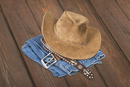 suede belt: Cowboy hat and accessories over  wood plank background with clipping path