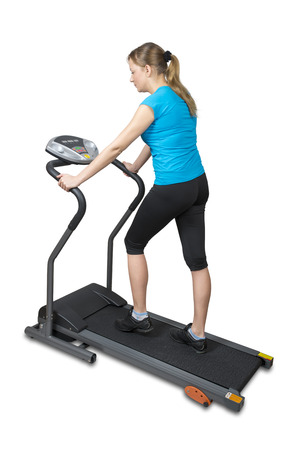 Young woman running on treadmill, isolated over white  photo