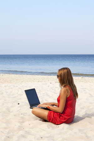 Woman is sitting with laptop on the beach  photo