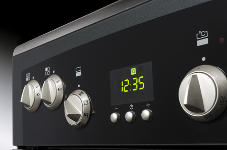 Close up of controls from a modern stainless steel oven with timer  Stock Photo