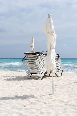sun bathers: Beach, beautiful weather, sun loungers and umbrellas waiting for tourists in Cancun, Mexico. This is one of the best beaches in the Mexico.
