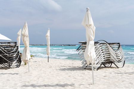 roo: Beach, beautiful weather, sun loungers and umbrellas waiting for tourists in Cancun, Mexico. This is one of the best beaches in the Mexico.