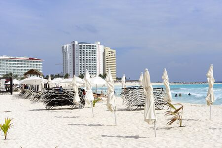 sun bathers: Beach, beautiful weather, sun loungers and umbrellas waiting for tourists in Cancun, Mexico.
