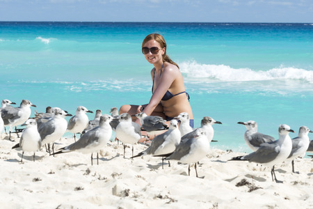 Young woman with seagulls on the beach in Cancun, Mexico. photo