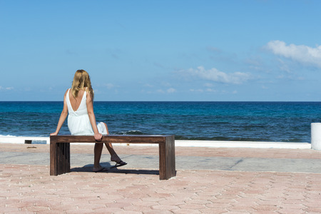 Woman sitting on the bench main promenade looking at the ocean on the Isla Mujeres in Mexico photo