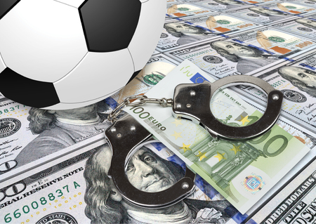 dishonesty: Soccer gambling corruption concept. Soccer ball with money and handcuffs.