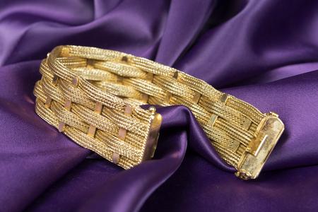 background purple: Gold bracelet isolated on purple satin background.