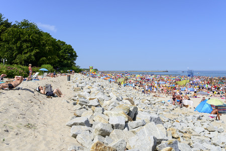 baltic people: Ustka, Poland - July 04, 2015: The scene on the beach in Ustka during the tourist season on a sunny day. A large group of people of all ages - are visible on the beach. The beach is located on the Baltic Sea.