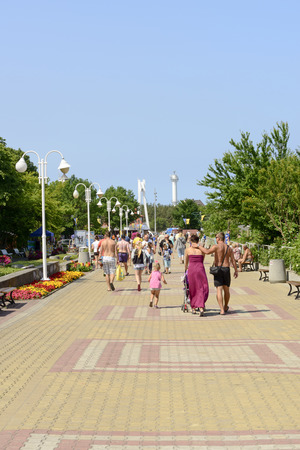 vacationing: USTKA - JULY 07: Promenade along the beach with the walking vacationing people on 7 July 2015 in Ustka, Poland.