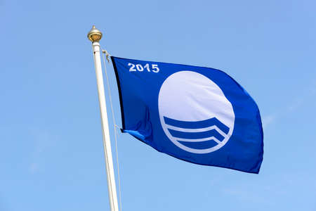 sightseers: Blue Flag - a symbol of ecological beaches at the seaside in Europe. Stock Photo