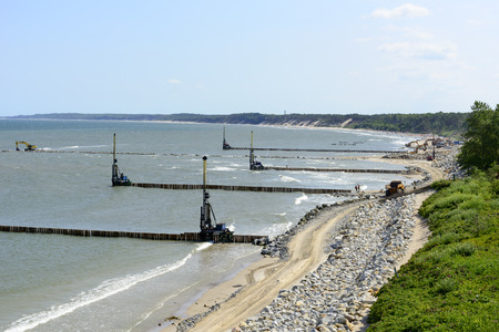 facilitate: Workers build a breakwater that Facilitate the construction of the beach in Ustka, Poland.