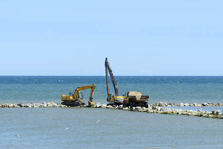 facilitate: Workers are building an artificial reef is Facilitate the construction of the beach on 7 July 2015 in Ustka, Poland.