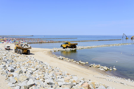 facilitate: Workers are building an artificial reef is Facilitate the construction of the beach on 4 July 2015 in Ustka, Poland. Editorial