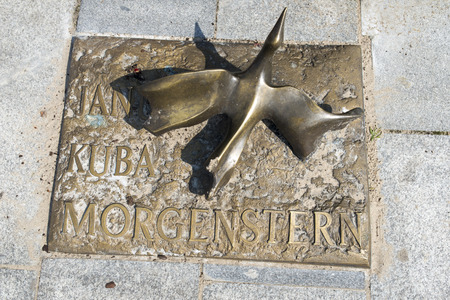 memorial plaque: The memorial plaque in brass on the sidewalk of famed Polish movie director Janusz Morgenstern at Avenue of Stars on 16 August 2015 in Miedzyzdroje, Poland.
