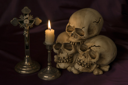 eye socket: Crucifix and a weathered human skull - Halloween background Stock Photo