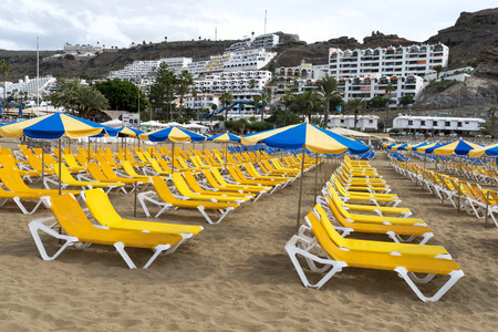 sunbeds: Empty sunbeds on the Atlantic ocean beach waiting for tourists in Puerto Rico, Gran Canaria Island. Editorial