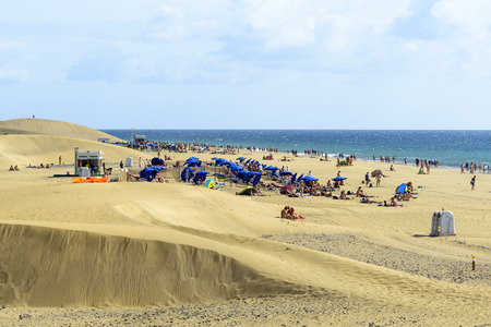 vacationing: Maspalomas sandy dunes with the walking vacationing LGBT people on the beach on 28 November 2015 in Maspalomas, Gran Canaria Island.