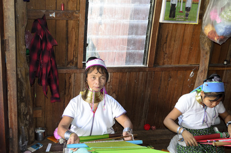 ethnology: Burmese women weaving silk clothe from lotus on November 2, 2014 in Inle Lake, Shan state, Myanmar. Silk fabric produced from lotus is a specialty of Inle Lake. Editorial