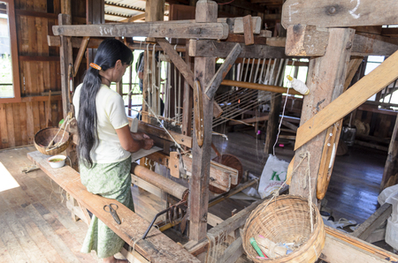 ethnology: Burmese woman weaving clothe from silk lotus on November 2, 2014 in Inle Lake, Shan state, Myanmar. Silk fabric produced from lotus is a specialty of Inle Lake. Editorial