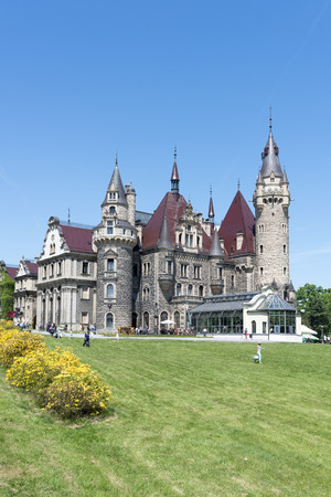 View of the Thiele-Winckler Palace on 22 May 2016 in the district Moszna, Poland. Tourists enjoying the beautiful weather visit the palace in Moszna. Editorial