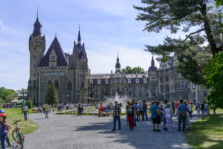 cloude: View of the Thiele-Winckler Palace from the park on 22 May 2016 in the district Moszna, Poland. Tourists enjoying the beautiful weather visit the palace in Moszna.