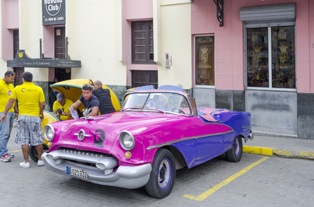 annuities: American classic car waiting for tourists on 29 November 2015 in Havana, Cuba. Brightly colored vintage American cars are very popular in Havana.