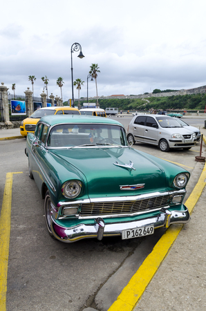 annuities: American classic cars waiting for tourists on 10 December 2015 in Havana, Cuba. Brightly colored vintage American cars are very popular in Havana. Editorial