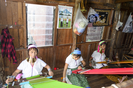 necked: Long necked Kayan Padaung women silk weaves on a loom in Their store at the Inle Lake on November 2, 2015 on Inle Lake, Myanmar (Burma).