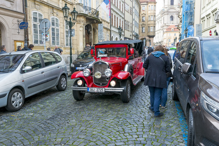 Old historic red car Prague on Mostovska street on October 15, 2016 in Prague, Czech Republic. Old cars are in Prague for tourists on tours of the city.