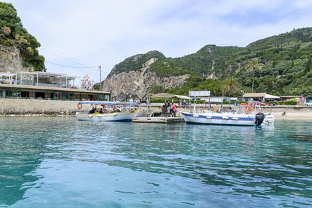 paleokastritsa: Tourists on the boat visit the caves on the Ionian Sea coast on May 15, 2017 in Paleokastritsa resort, Corfu island in Greece. Editorial