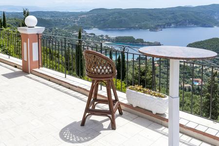 paleokastritsa: Empty chair and table with a wonderful view of the Paleokastritsa coast. Corfu island, Greece. Stock Photo