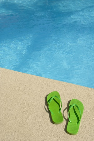 Bright green Flip flops by  the pool photo