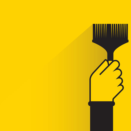 hand holding paint brush on yellow background
