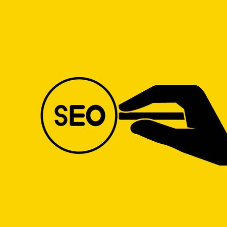 hand holding magnifier seo on yellow background