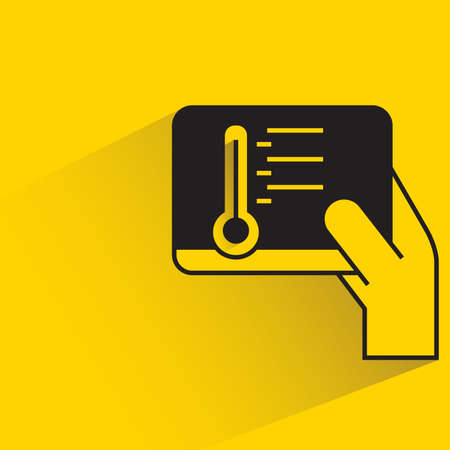 hand holding tablet controlling thermometer with shadow on yellow background