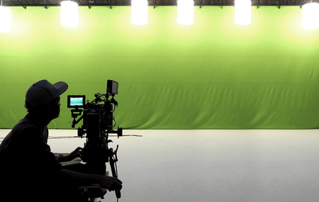 Camera man and tools and white floor and big green screen studio.