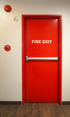 Emergency fire exit door and red color and white wall in building.