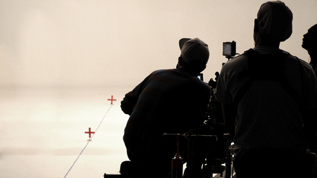 Behind the scenes or making of film in the studio and silhouette of camera man.