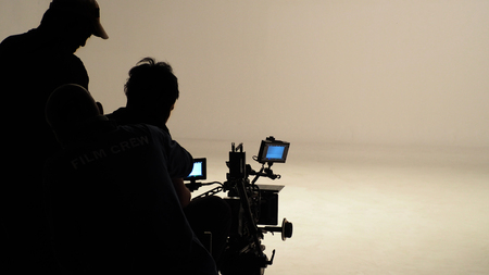 Silhouette of working people or production film crew are making movie or shooting tv online content live show in studio with camera equipment set. Stock Photo