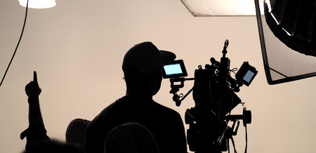 Behind the scene of tv movie video film shooting production crew team and camera lighting set in the big studio.