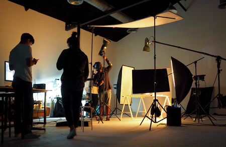 Silhouette of people working in production studio for shooting or recording by digital camera and lighting set.