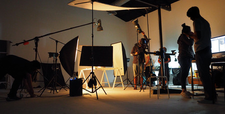 Behind the shooting production crew team and silhouette of camera and equipment in studio.