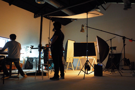 director: Behind the shooting production crew team and silhouette of camera and equipment in studio.