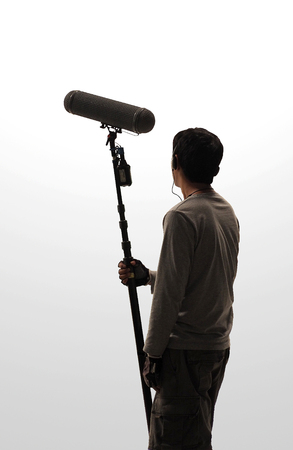 Boom Microphone hold up high by video or film production crew team man and recording sound for movie in a big studio. Stock Photo