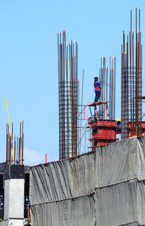 Labor working on construction site that have industry material on high building and have high risk in danger on thier life.