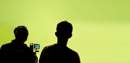 Behind the video production camera set and crew team shooting in a big green screen studio.