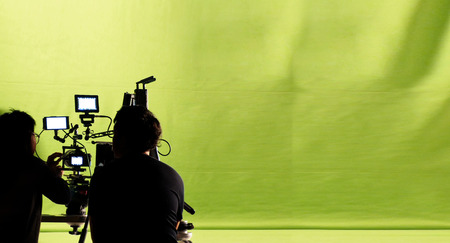 film crew: Behind the video production camera set and crew team shooting in a big green screen studio.