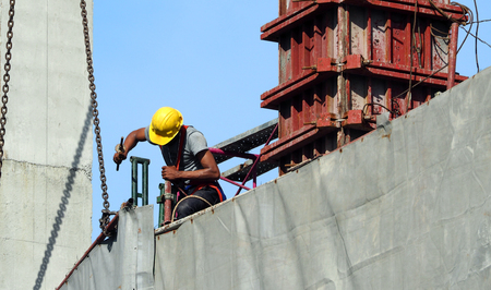 Labor man working on construction site with helmet and safty equipment and covering the building with grey color vinyl and blue sky.
